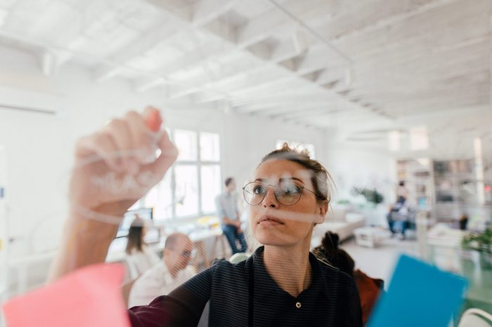 Photo of a young woman writing on a transparent wipe board and thinking of a solution for her work-related problems