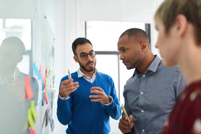 Multi-ethnic group hipster trendy business people discussing during a brainstorm session for their small company