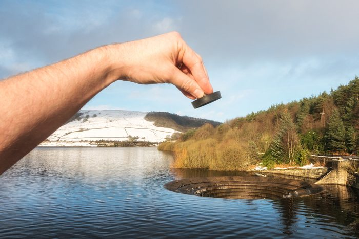 Human hand holding a sink plug, appearing to be pulled from a lake at Ladybower reservoir spillway.