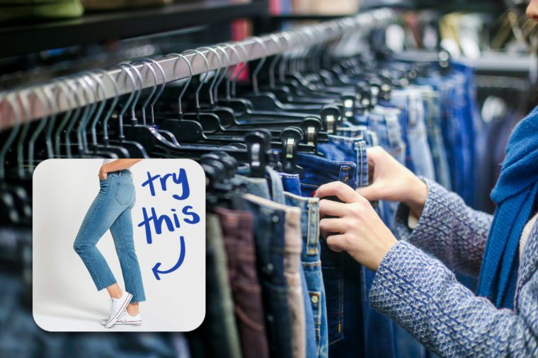 woman's hands browsing jeans on a rack