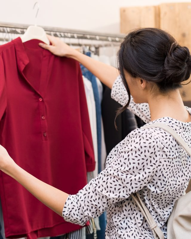 Woman choosing blouse from new collection of clothes in a boutique