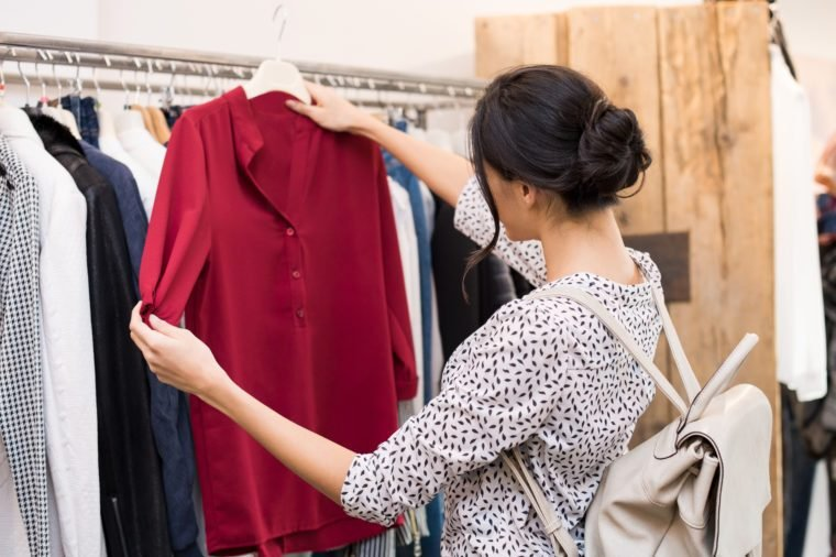 Woman choosing blouse from new collection of clothes in a boutique. Beautiful woman choosing clothes in a clothing shop. Rear view of girl doing shopping.