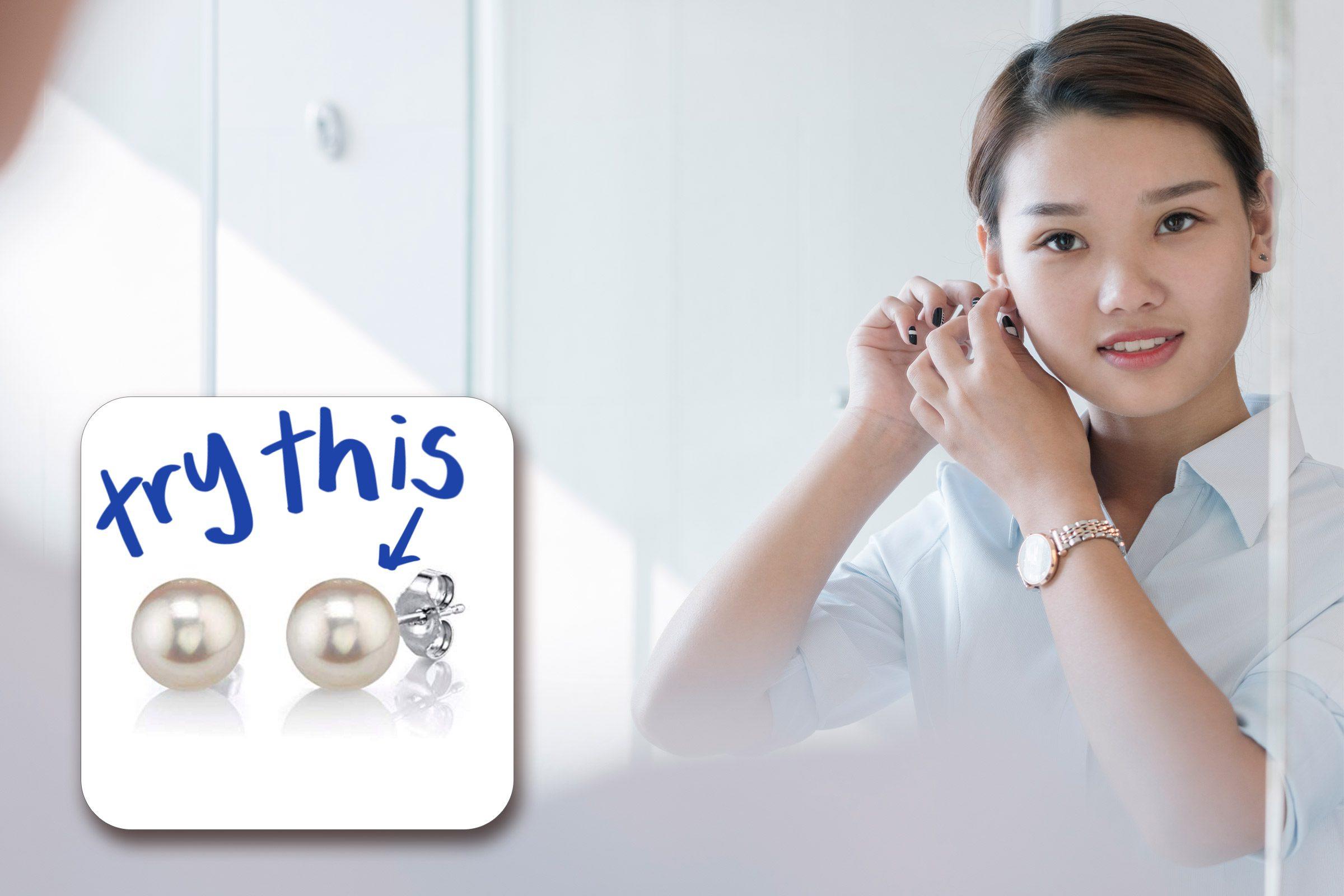 woman putting in earrings in the mirror