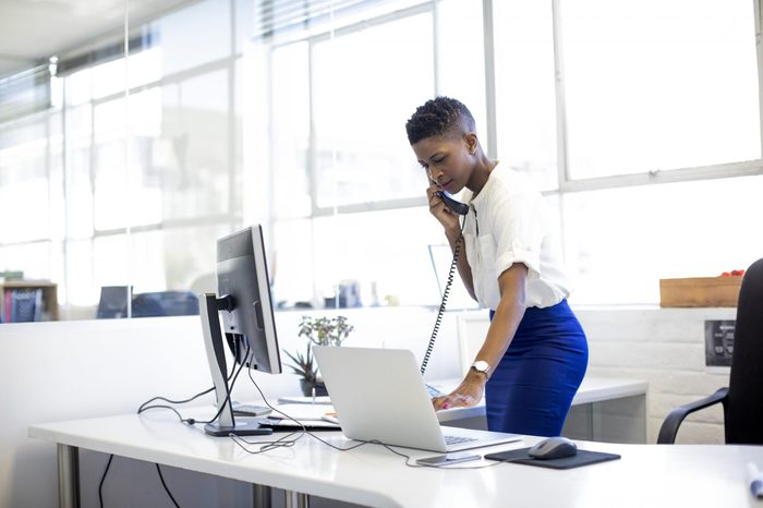 Mid adult businesswoman talking on landline phone while using laptop. Female professional is using technologies while standing in creative office. She is wearing smart casuals.