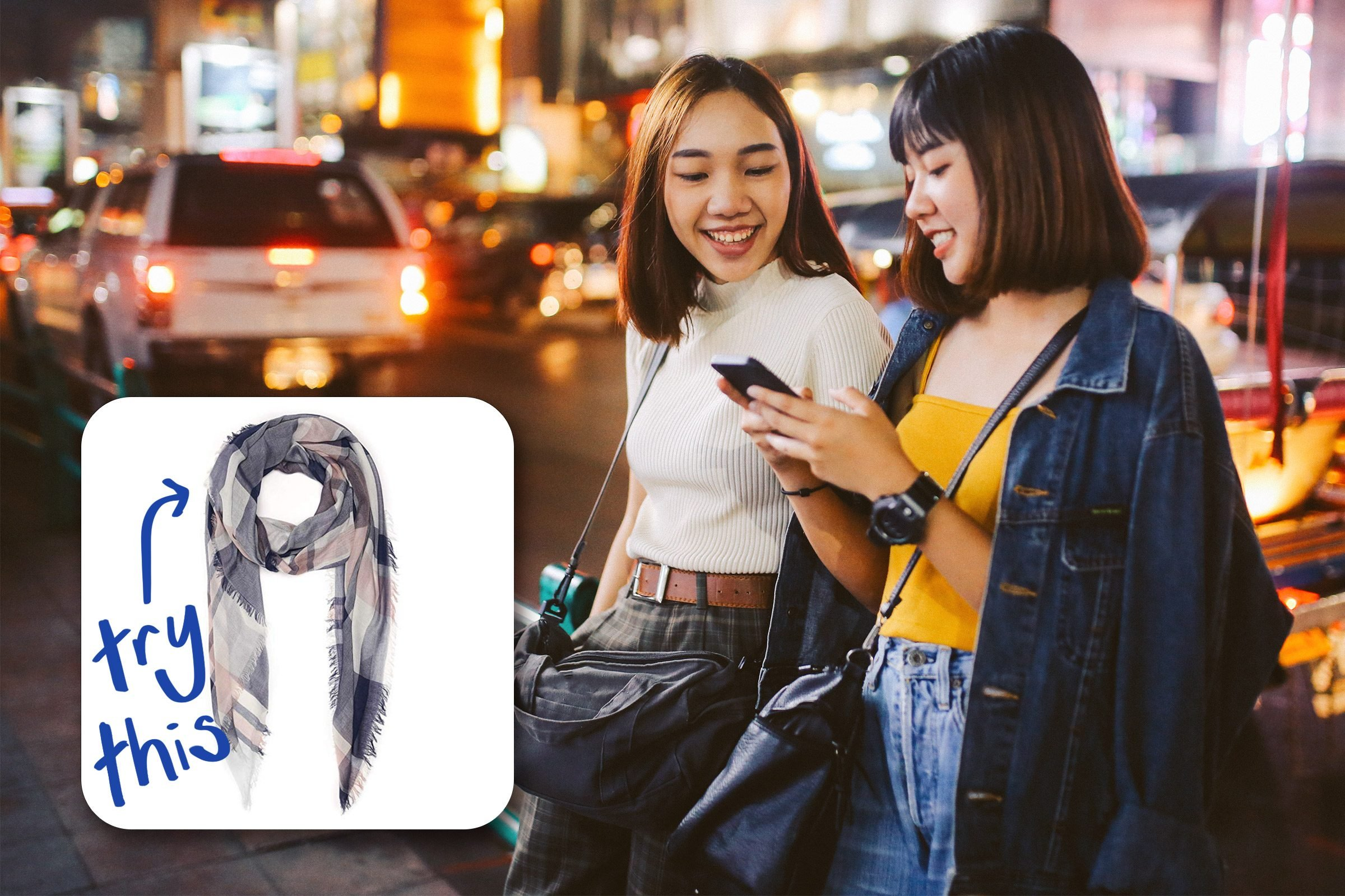 two trendy friends looking at a phone. try this scarf.