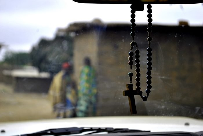 Rosary hanging in a car. Silhouette of African women in Angola.