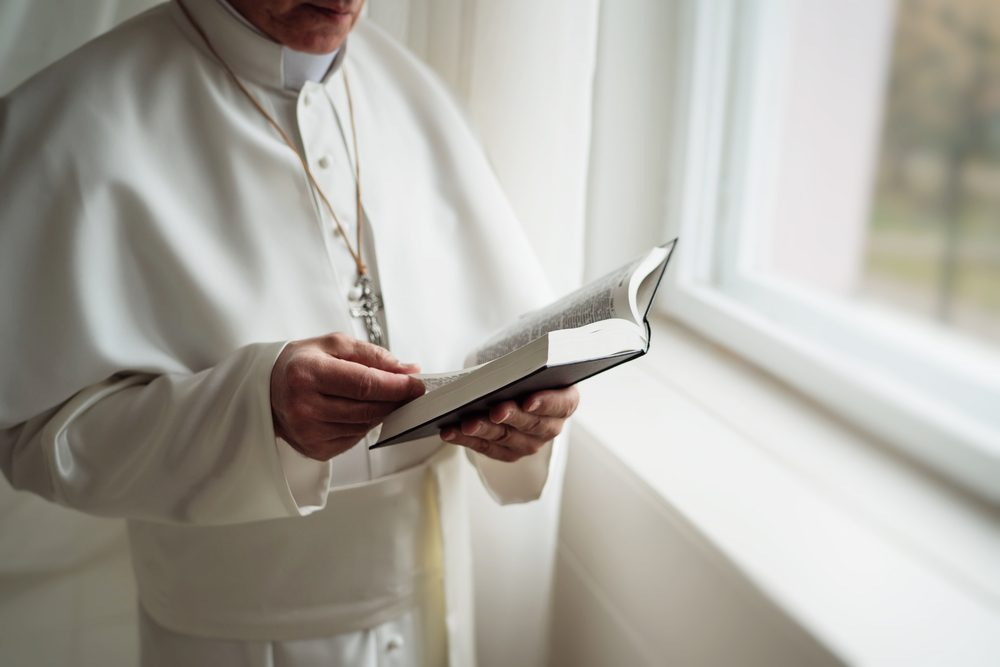 Pope reads the Bible in his office.