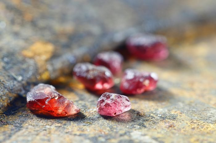 Uncut gemstones, red almandine garnets, from Lapland, displayed on a rusty gold pan