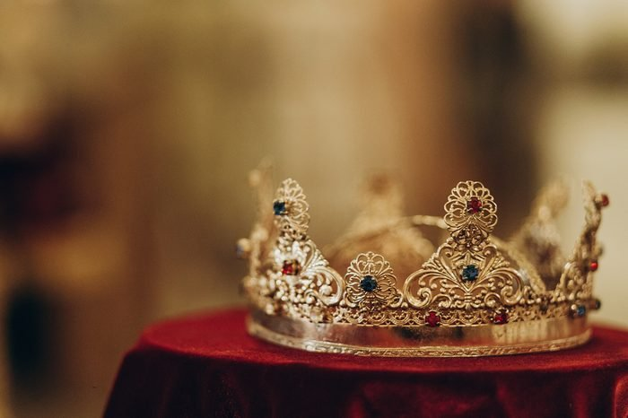 golden crown with gemstones on red napkin on altar in church. traditional wedding ceremony, space for text. religion