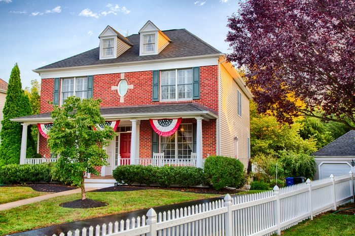 A colonial house in Medford, New Jersey with American Flag buntings on the porch.