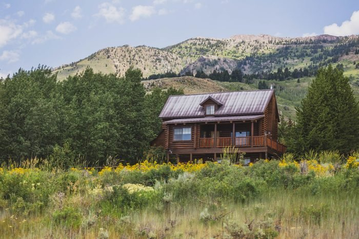Quaint house on hillside in green mountain landscape of central Montana.