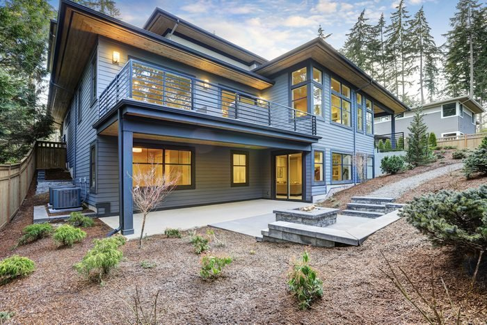 Luxury new construction home with blue wood siding. Patio area with fire pit on the first floor and deck with outdoor furniture on the second. Northwest, USA