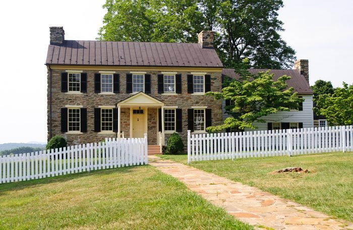 historic house and white pickett fence on a hill