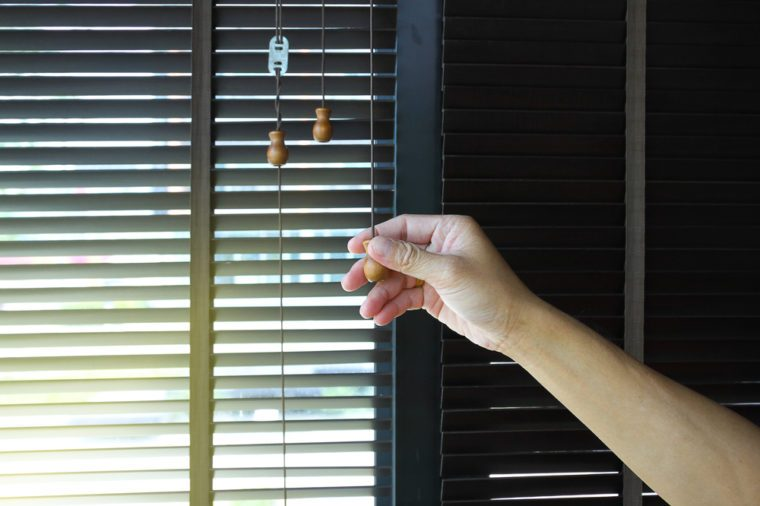 Man hand holding a wooden blinds decoration in livingroom