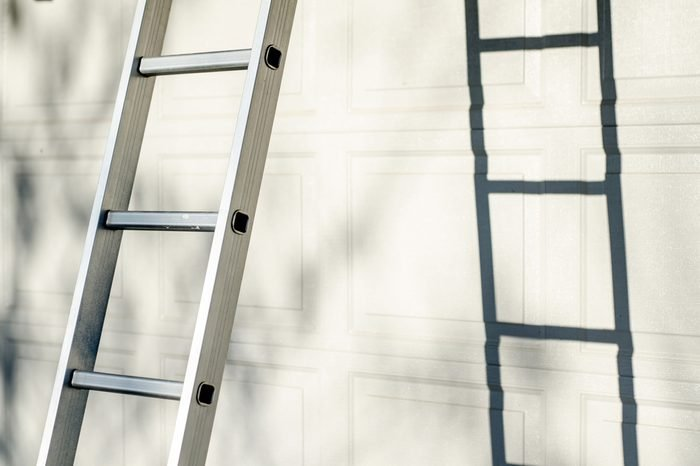 Aluminum ladder leaning against white garage door, with strong shadow and warm natural sun light