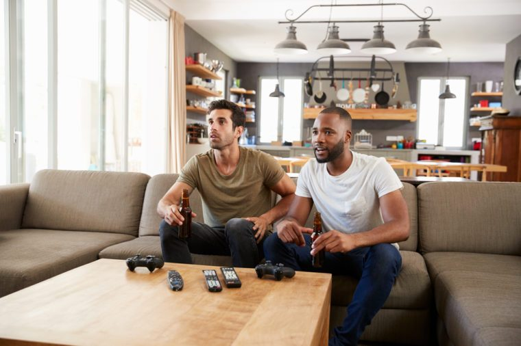 Two Male Friends Sit On Sofa And Watch Sports On Television