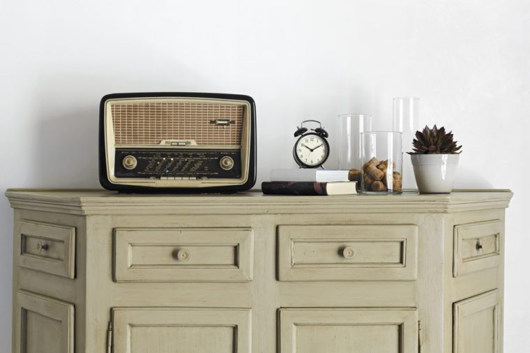 old radio and alarm-clock on the book on old sideboard