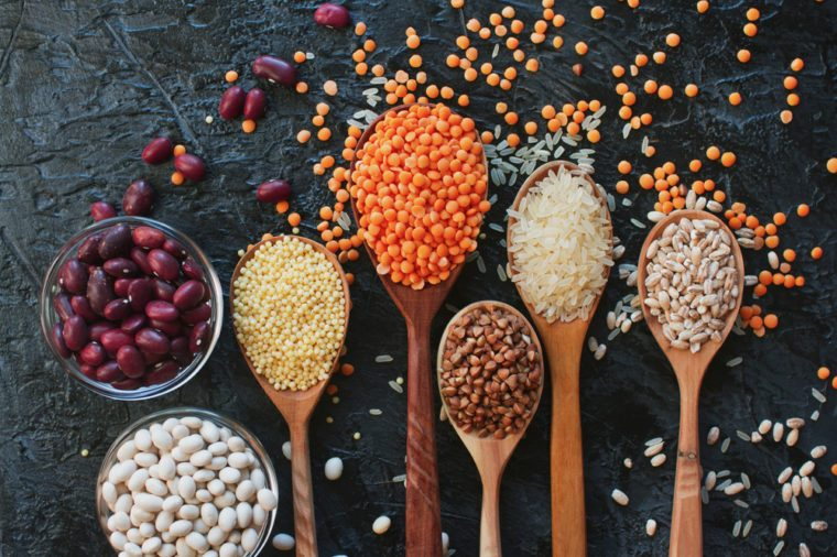 Raw organic cereal grains, seeds and beans (millet, rye,wheat, buckwheat, red and white beans, lentil, rice) in wooden spoons and bowls on dark stone background, top view. Healthy eating concept
