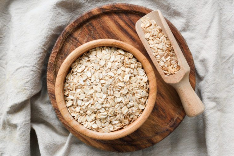 Rolled oats, organic oat flakes in wooden bowl on wooden background. Healthy lifestyle, healthy eating, vegan food concept