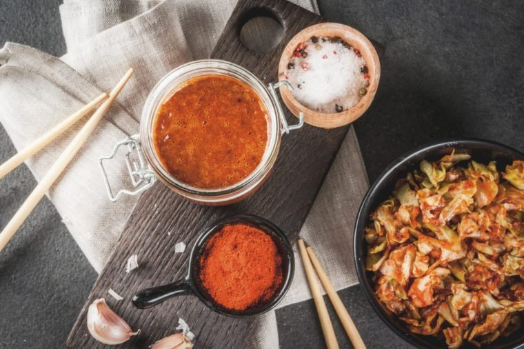 Asian cuisine. Fermented food. Traditional Korean dish: kimchi cabbage - sauerkraut with traditional kimchi sauce from chili pepper, garlic, spices, salt. On a black stone table. Copy space top view