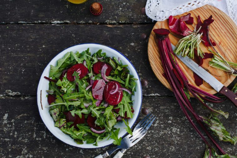 Preparing salad with dandelions, red beets and red onion. Fresh organic vegetables. Food dark background. Healthy herbs from garden