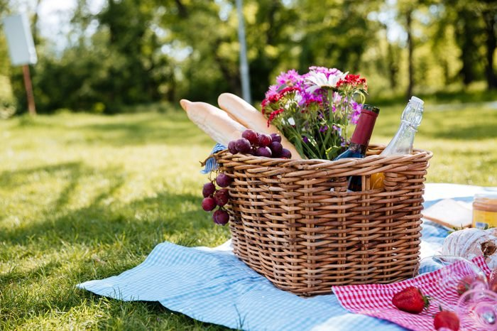 Closeup of picnic basket with drinks, food and flowers on the grass