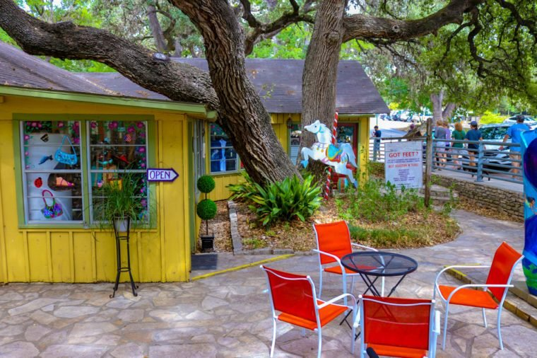 This beautiful photo of a patio shaded by a large Texas Oak Tree in front of a yellow gift shop in Wimberley TX.