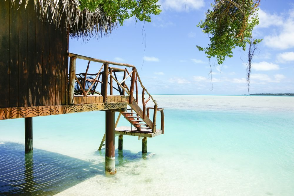 Tropical cabin over waters edge, Cook Islands, South Pacific.