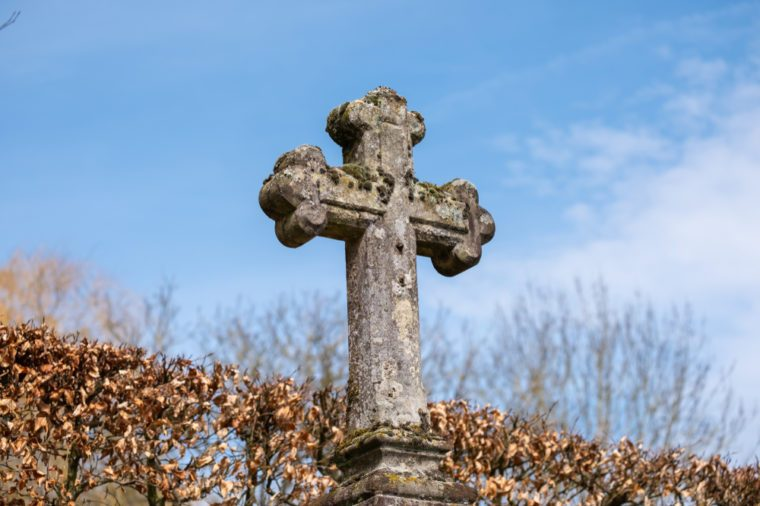 Old weathered stone cross crucifix on cemetary in Girsterklaus, Luxxembourg.
