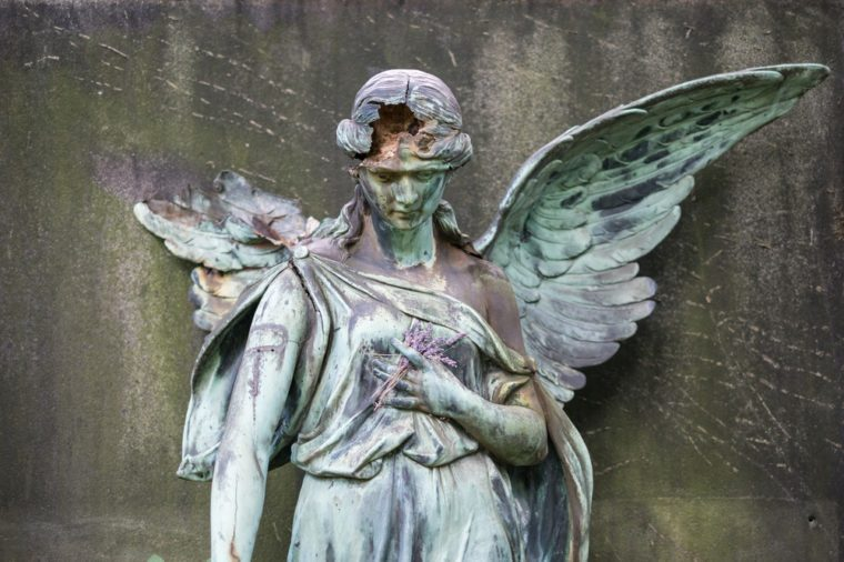 damaged sculpture of a female angel statue on cemetery