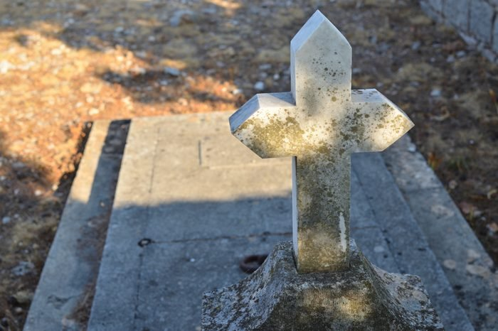 Old stone cross of a grave with a grave ledger