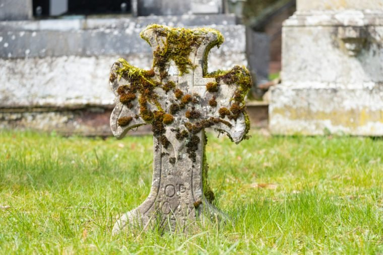 Ancient stone cross with moss on graveyard in Girsterklaus, Luxembourg.