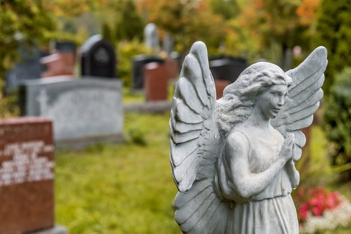 Angel statue praying in front of several headstones on a graveyard in Fall, in a cemetery.