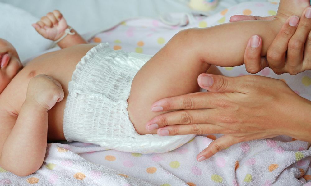 Close up of mother hands put on a baby diaper to her newborn.