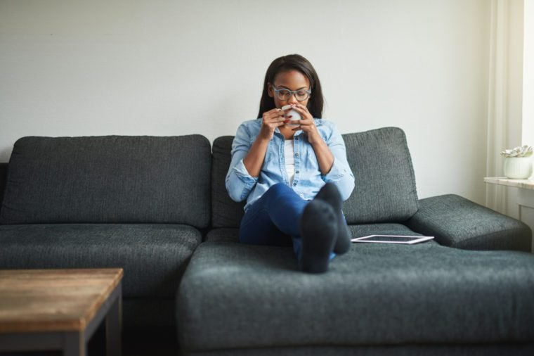 Young African woman sitting on her living sofa at home drinking a cup of coffee and relaxing