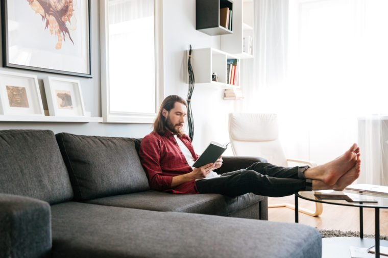 Handsome bearded young man sitting and reading book on sofa at home