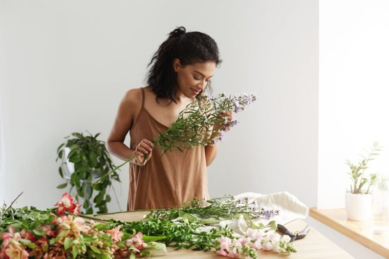 Attractive african female florist smiling making bouquet at workplace over white wall.