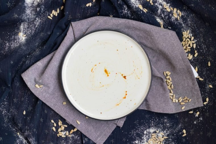Dirty and empty diss, plate left after finished breakfast, lunch or dinner. Plate with pieces of crumbs and pieces. Kitchenware concept for restaurants and cafes.