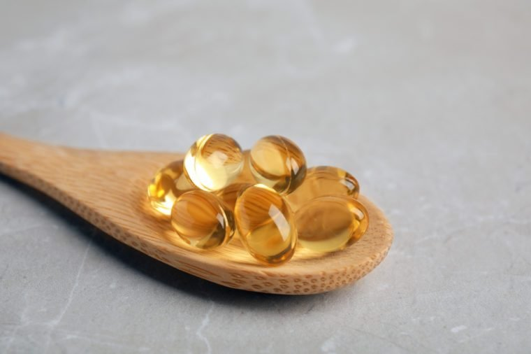 Spoon with cod liver oil pills on table, closeup