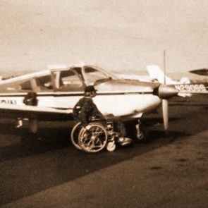 Pat Patterson in wheelchair next to plane