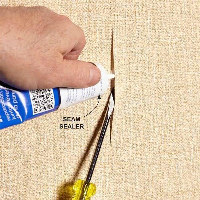 man fixing wallpaper