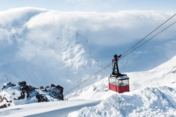 Old red cable car at mountain. Ski resort Elbrus. Caucasus, Russian Federation. Beautiful winter landscape with snow covered mountains.