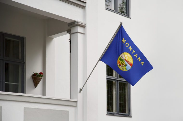 Montana flag. Montana state flag hanging on a pole in front of the house. State flag waving on a home displaying on a pole on a front door of a building. Flag raised at a full staff.