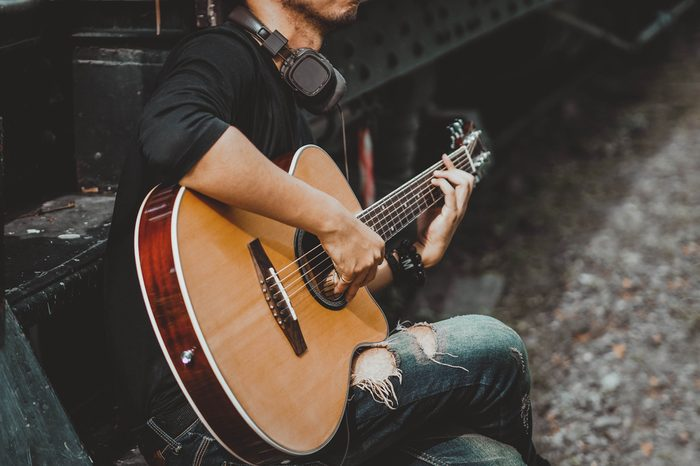 Handsome man musician playing the guitar
