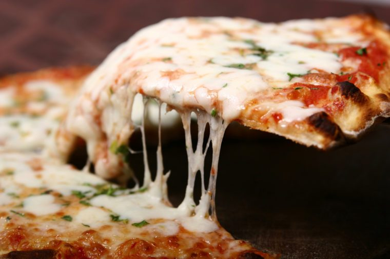 Pizza slice-lifted with cheese strings