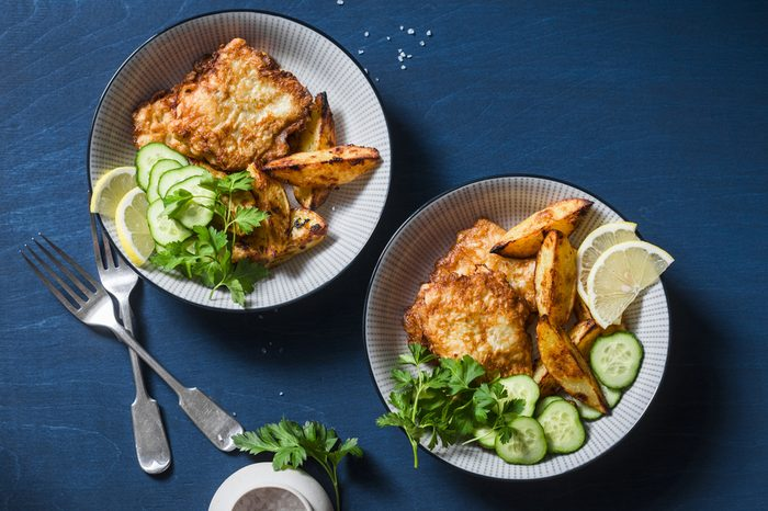 Two bowls with deep-fried fish and garlic baked potatoes on a blue background, top view. Fish and chips. Flat lay