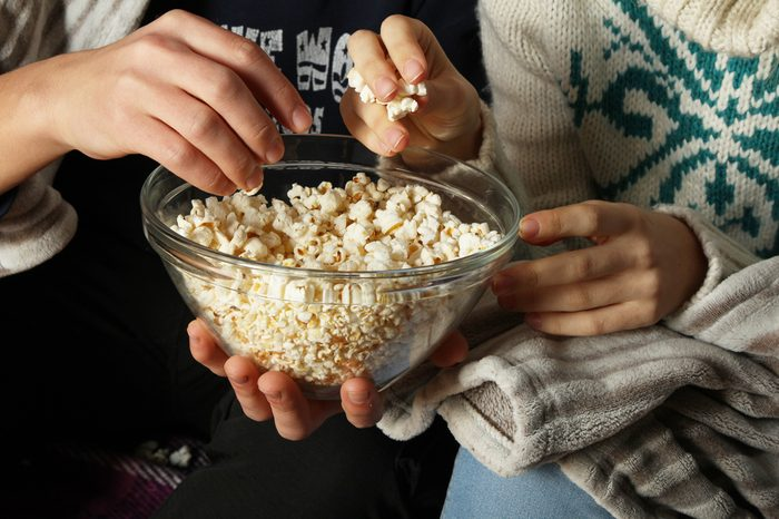 Young people watch movies and eating popcorn with a glass bowl, close-up