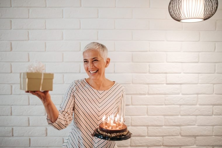 Mature woman holding a birthday cake and a gift