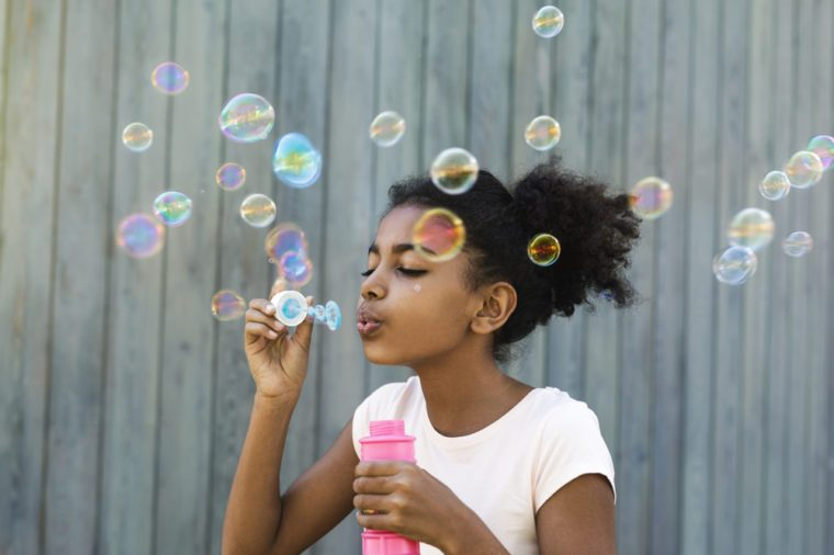 Portrait of cute girl blowing bubbles outdoors