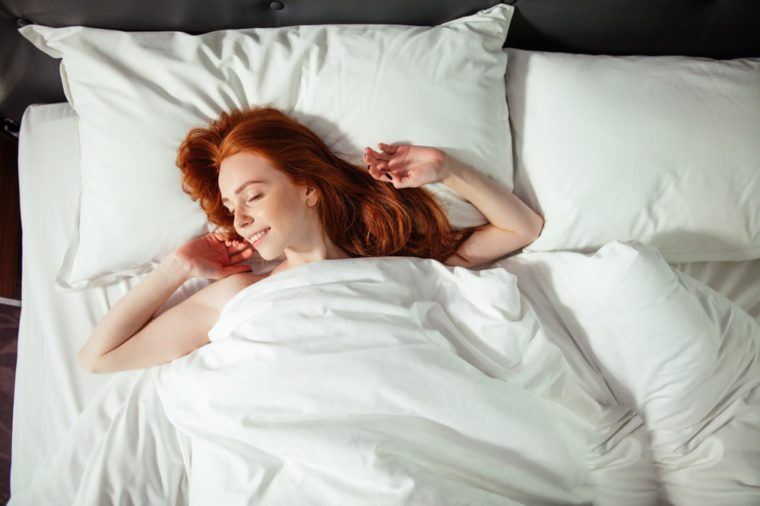Redhead sleeping young woman lies in bed with eyes closed. top view